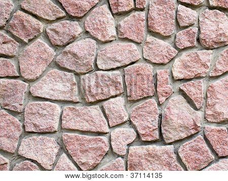 Red granite masonry wall closeup background.