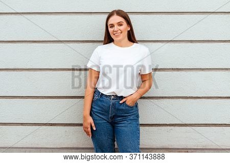 Young Attractive Girl Wearing A White T-shirt Standing On A Grey Wall Background