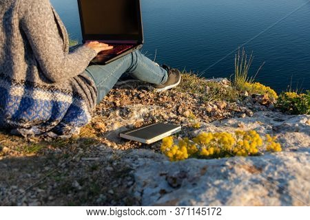 A Girl Is Working On A Laptop At The Top Of A Mountain. Remote Work And Training In Nature. Sea View
