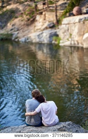 The Guy And The Girl Are Sitting On A Cliff Above The River And Looking In Front. Rear View. Loving