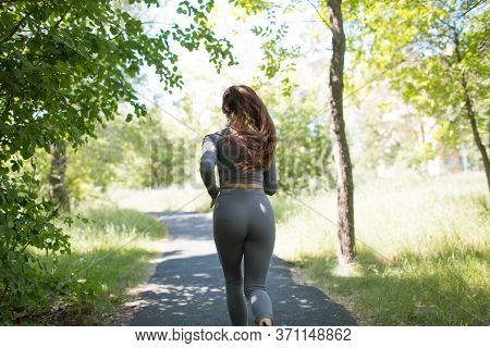 Back Rear View Running Girl In City Park. Young Positive Woman Runner Outdoor Jogging