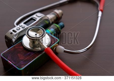 Conceptual Image Of Uncertainty Of Health Safety Of E-cigarettes. Isolated Close-up Red Stethoscope
