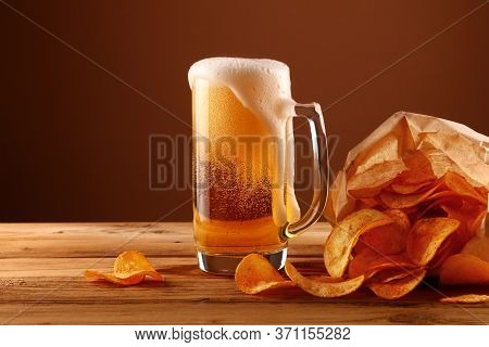 Close Up One Glass Mug Of Lager Beer With White Froth And Bubbles And Paper Bag Of Potato Chips On W