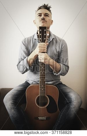 Handsome Man In Casual Clothes Is Posing With His Acoustic Guitar. Guy With Guitar Sitting On Sofa I