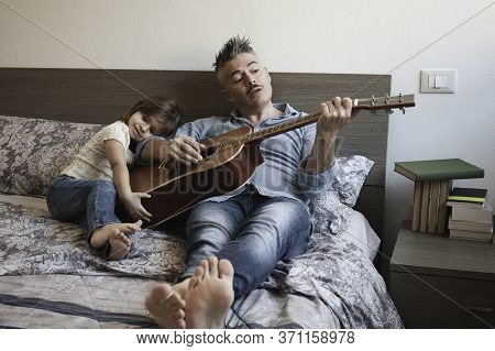 Cool Daddy Playing The Acoustic Guitar And Singing A Song While His Daughter Listens To Him With A D