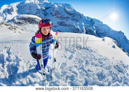 Full Height Portrait From Side Of Smiling Skier Girl With Ski Standing In Snow Over Mountain Summit