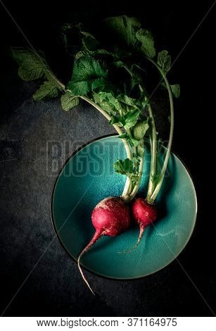 Red radish placed  in a colorful bowl. Small two radishes with leaves shot from above on dark background.