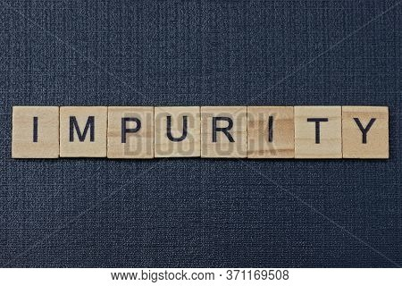 Text On Word Impurity From Gray Wooden Letters On A Black Background