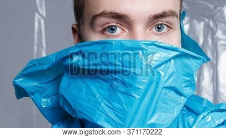 Ecological Content. Frontal Portrait Of A Young Man With Blue Eyes, Have Covered Mouth With Blue Pla