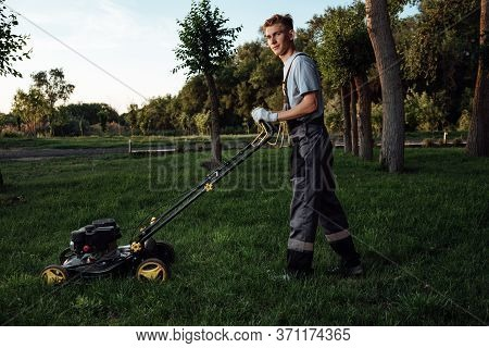A Young Male Gardener In Overalls Uses A Lawn Mower.
