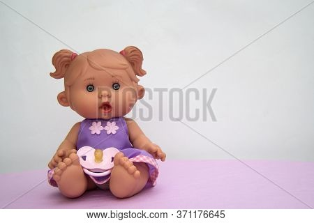 A Small Vinyl Doll With Blue Eyes Sits On A Pink Surface. She's Wearing A Sundress And She's Got A N