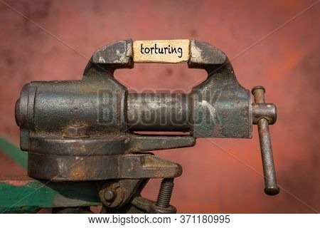 Concept Of Dealing With Problem. Vice Grip Tool Squeezing A Plank With The Word Torturing
