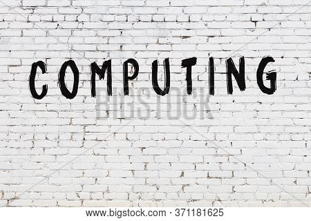 White Brick Wall With Inscription Computing Handwritten With Black Paint