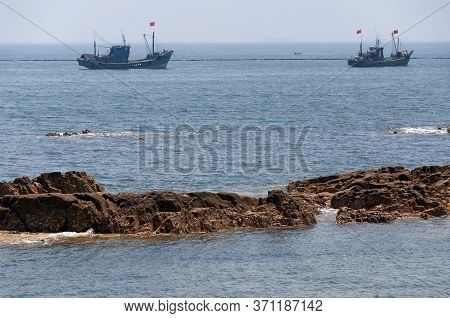 Two Chinese Fishing Boats Moored Offshore In Fushan Bay Near Qingdao China In Shandong Province On A