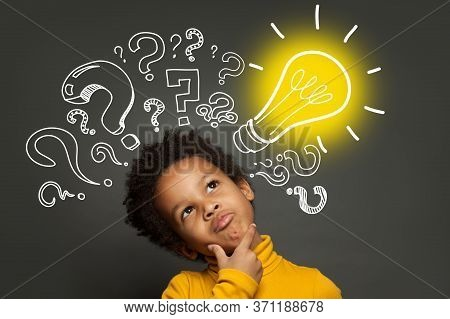 Thinking Child Boy On Black Background With Light Bulb And Question Marks. Brainstorming And Idea Co