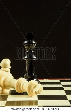 On The Piece Of The Chessboard Is A Black Figure Of The King, And Around It Lie The White Pieces Def
