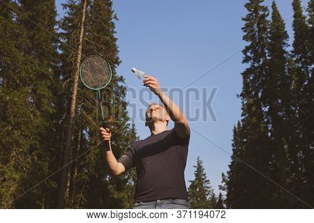 Young Caucasian Man Plays Badminton On A Background Of Blue Sky And Forest. The Concept Of An Amateu