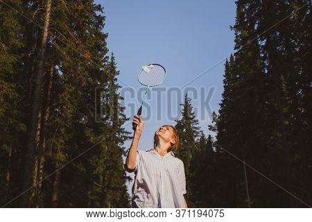•	Young Caucasian Woman Plays Badminton On A Background Of Blue Sky And Forest. The Concept Of An Am