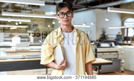 Portrait Of Young Ambitious Businessman In Casual Wear And Glasses Looking At Camera And Holding Lap