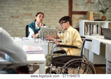 Portrait Of Young Male Office Worker In A Wheelchair Talking To Female Colleague While Showing Her I