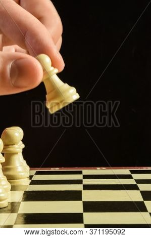 On The Chessboard Are Left White Chess Wooden Pieces Pawns. Above Them Hung A Human Hand, Which Walk