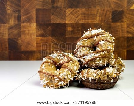 Pile Of German Chocolate Donuts / Doughnnuts On A White Counter With A Wooden Wall Behind.  Chocolat