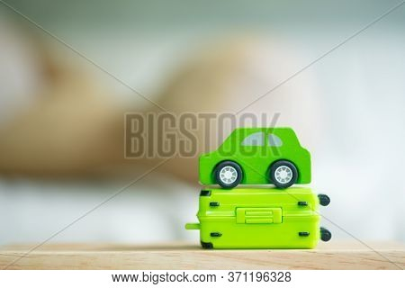 Miniature Green Car On Miniature Green Suitcase. Concept Of Travel