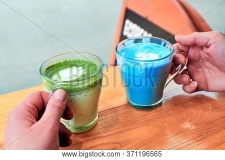 Blue Latte, And Green Latte In Two Female Hands. Friends Meet At Cafe By The Window. Trendy Variatio