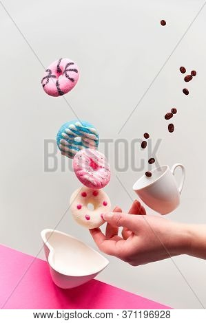 St. Valentine Concept, Levitation Of Doughnuts Above Heart Shaped Bowl. Coffee Beans Fly In Espresso