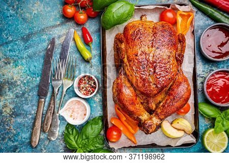 Roasted Chicken With A Golden Crust With Vegetables On A Blue Background, Top View