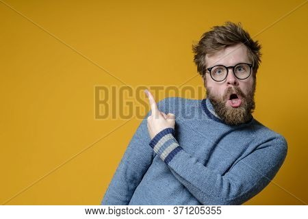 Odd Bearded Man In Glasses Points With An Index Finger To An Empty Place And Stands In A Bizarre Pos