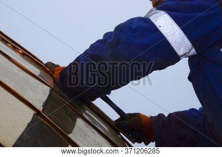 Assembling The Gilded Dome Of An Orthodox Church. The Master In Working Gloves, Collects Parts Of Th