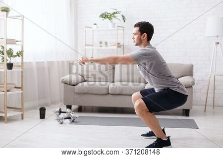 Stay Home Alone To Workout. Young Man Doing Squats Exercises In Living Room Interior At Home, Free S