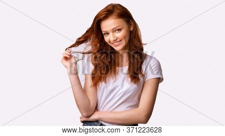 Pretty Millennial Girl Playing With Red Hair Posing Smiling To Camera In Studio On White Background.