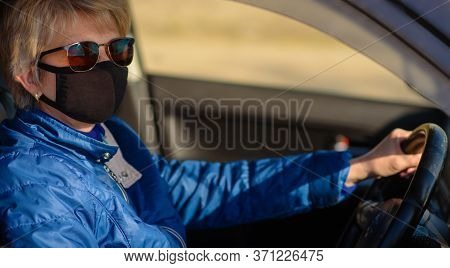 Pensioner Woman In Face Mask And Sunglasses Is Driving A Car During Coronavirus Pandemic And Lookiin