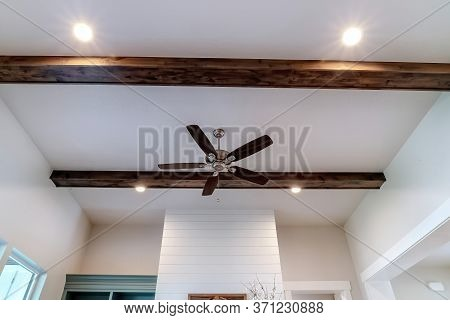 Ceiling Fan With Lights Between Decorative Wood Beams Inside Living Room Of Home