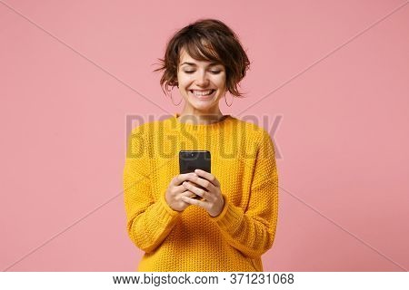 Cheerful Young Brunette Woman Girl In Yellow Sweater Posing Isolated On Pastel Pink Wall Background