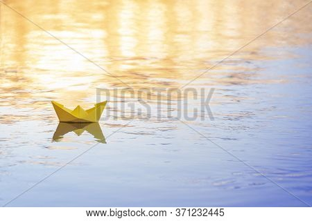 Yellow Paper Ship Floating On Water, Origami Paper Boat On A Big River At Sunset, Concept Of Travel,
