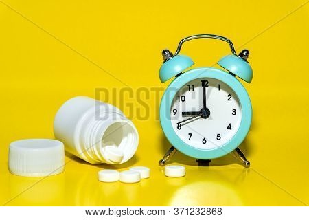 Alarm Clock, Pills, A Jar Of Medicine On Yellow Background. Awakening Up Early In The Morning By Cal