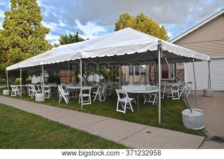 A Huge Outdoor Party Canopy Is Placed In The Front Yard Of A High School Graduate For Celebration.