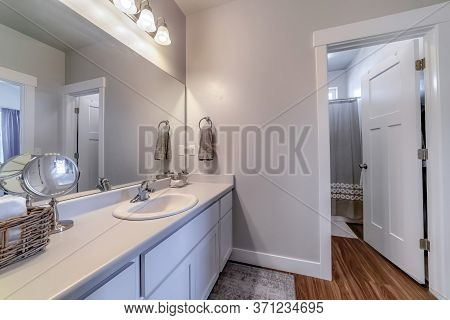 Vanity Area Of Bathroom With Door That Leads To The Toilet Bathtub And Shower