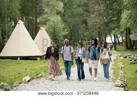 Group of young multi-ethnic people arrived at campsite walking over beautiful park