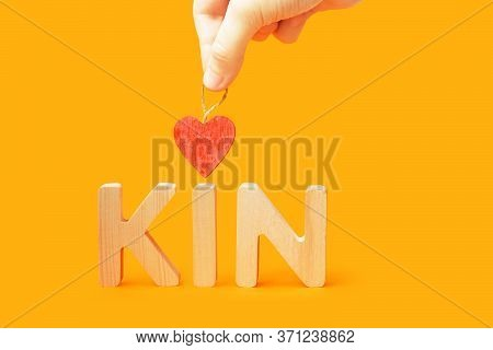 Word Kin On Orange Background. Family Concept. Hand Holds Heart Over The Word Kin