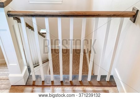 U Shaped Stairway Of Home With Brwon Handrail Supported By White Balusters