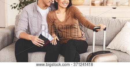 Honeymoon Vacation. Unrecognizable Asian Spouses Waiting For Travel Sitting With Packed Suitcase And
