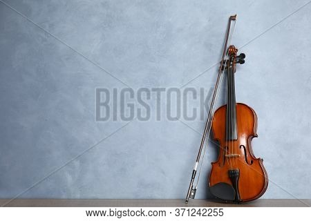 Beautiful Violin And Bow On Wooden Table Near Light Blue Wall. Space For Text