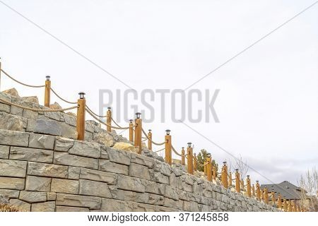 Rope Fence With Lamps On Posts Lining A Retaining Wall Made Of Stone Blocks