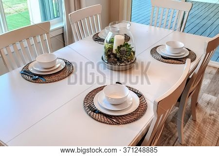 Dinner Table Setting With Tableware On Placemats Arranged Around A Centerpiece