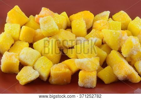Closeup Of Frozen Mango Fruit Chunk Cubes With Ice Crystals On Red Plate