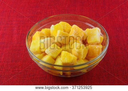 Frozen Mango Fruit Chunk Cubes With Ice Crystals In Glass Ingredient Bowl On Red Tablecloth